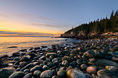 Rocky beach in Acadia National Park, Maine with view of Otter Cliffs at sunrise.