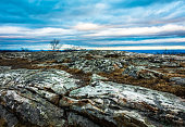 Rocky granite outcroppings under a beautiful blue cloudy sky at dusk, High Point Monument at the top of NJ in winter