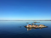 Rocky Island in a fjord of sweden, blue sky, blue calm water, red house and small lighthouse, very calm scene