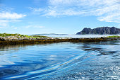 Beautiful nature with blue sky, reflection in water, rocky islands, Norway