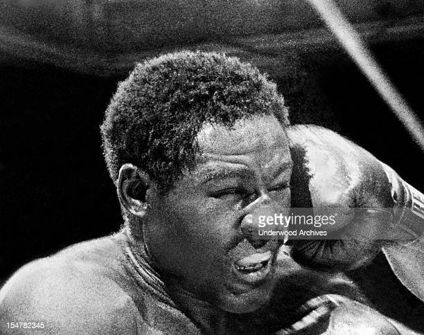 Rocky Marciano launches a right fist to the left side of Ezzard Charles face in the sixth round of their heavyweight title bout in Yankee Stadium...
