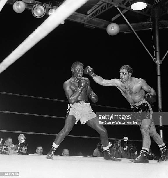 Rocky Marciano throws a right hook against Ezzard Charles during their bout at Yankee Stadium on September 171954 in Bronx New York Rocky Marciano...