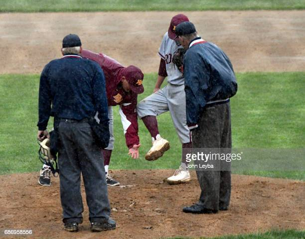 Rocky Mountain coach Scott Bullock checks the cleats of Kalen Hammer as mud starts to build up on them on the mound against Mountain Vista during the...
