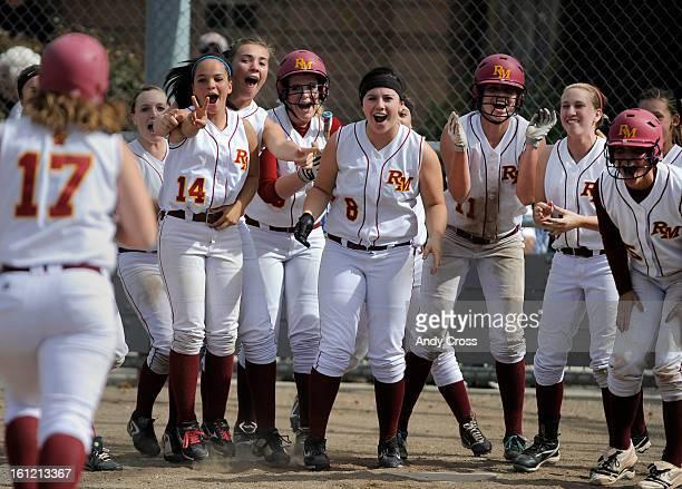 LOVELAND CO Rocky Mountain Lobos girls softball team awaits teammate Megan Rhead at home plate after Rhead hit a tworun home run in the second inning...