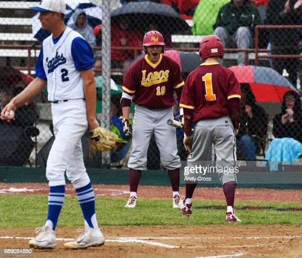 Rocky Mountain Lobos outfielder Hayden Heinze #1 celebrates with teammate Spencer Gendreau #19 after Heinze scored on a wild pitch by Broomfield...