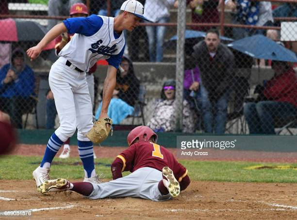 Rocky Mountain Lobos outfielder Hayden Heinze #1 crosses home plate before Broomfield pitcher Blake Rohm can tag him scoring a run in the first...