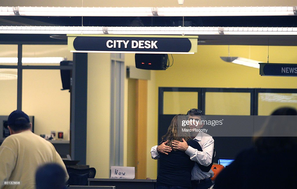 Rocky Mountain News editor, publisher and president John Temple hugs Judy DeHaas, a staff photographer at the paper, in the newsroom February 26, 2009 in Denver, Colorado. Executives with parent company E.W. Scripps announced to employees that tomorrow's edition of the News would be its last after almost 150 years of publishing. The newspaper had been put up for sale by Scripps, but the search for a buyer proved unsuccessful. The closure will cost 228 newsroom employees their jobs.