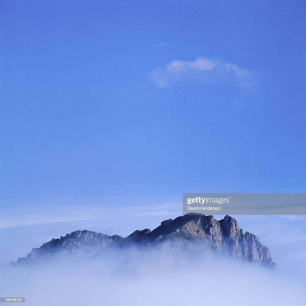 Rocky mountain surrounded by clouds : Stock Photo