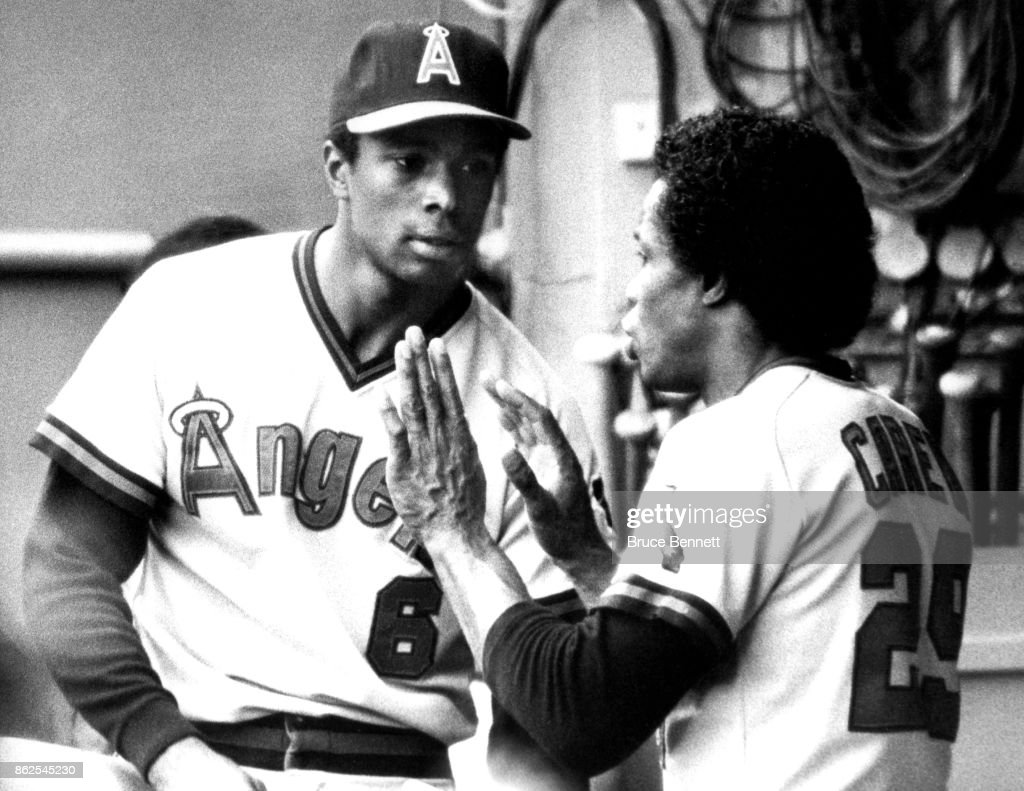 Rod Carew #29 of the California Angels gives some pointers to teammate Daryl Sconier #6 on how to play first base during an MLB game against the Cleveland Indians on June 14, 1983 at Cleveland Stadium in Cleveland, Ohio.