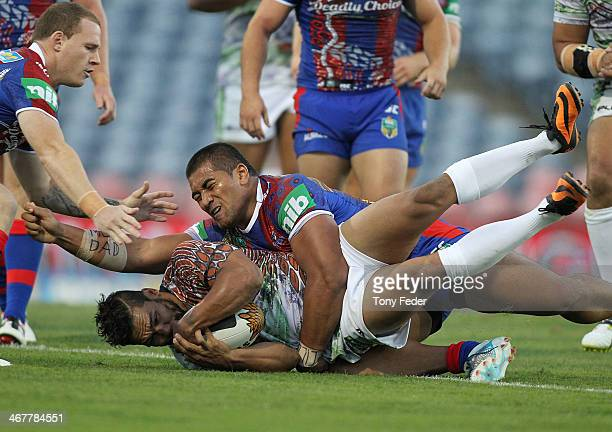 Rod Jensen of the Goannas scores a try while being tackled by Sione Mata'Utia of the Knights during the NRL trial match between the Newcastle Knights...