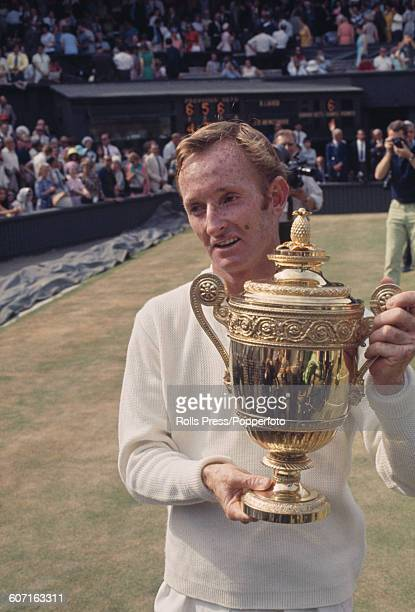 Rod Laver of Australia stands holding the Gentlemen's singles trophy after winning the Men's Singles final against his fellow countryman Tony Roche...