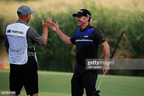 Rod Pampling of Australia celebrates with his caddie after putting for birdie to win on the 18th green during the final round of the Shriners...