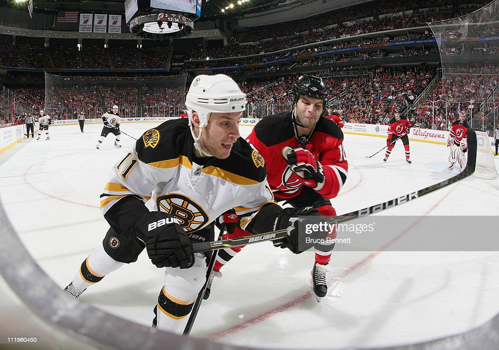 Rod Pelley of the New Jersey Devils checks Gregory Campbell of the Boston Bruins at the Prudential Center on April 10 2011 in Newark New Jersey The...