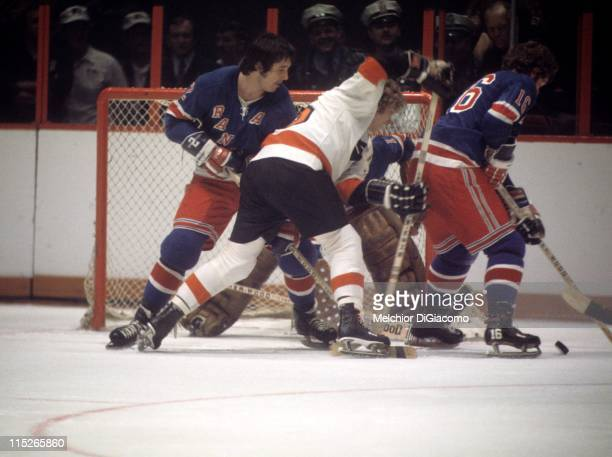 Rod Seiling of the New York Rangers skates with the puck as Bobby Clarke of the Philadelphia Flyers tries to score while being defended by Brad Park...