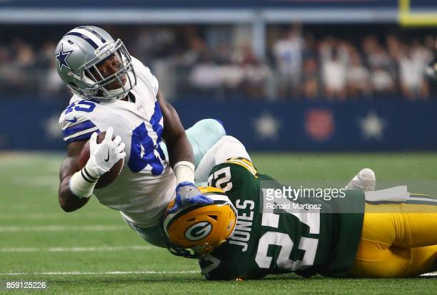 Rod Smith of the Dallas Cowboys is brought down b Josh Jones of the Green Ba Packers after a leaping catch in the first half of a football game at...