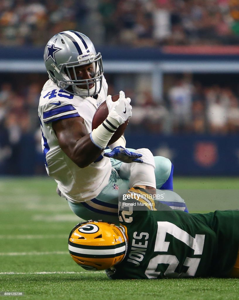 Rod Smith #45 of the Dallas Cowboys is brought down b Josh Jones #27 of the Green Ba Packers after a leaping catch in the first half of a football game at AT&T Stadium on October 8, 2017 in Arlington, Texas.