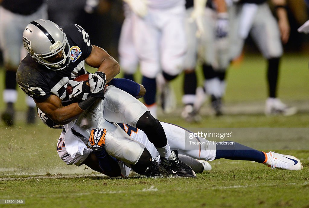 Rod Streater #80 of the Oakland Raiders after a short reception gets dragged down from behind by Champ Bailey #24 of the Denver Broncos at Oakland-Alameda County Coliseum on December 6, 2012 in Oakland, California.