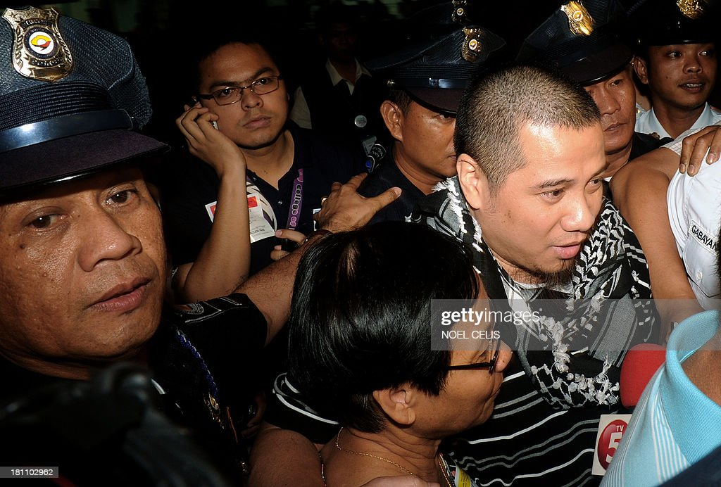 Rodelio 'Dondon' Lanuza, 38, (R) and his mother Letty (bottom C) arrive at Manila International Airport on September 19, 2013. Lanuza spent nearly 13 months in a Saudi Arabian prison for the murder of a man he accused of attempting to sexually assault him, for which he was sentenced to die. He was granted a royal reprieve in February after the victim's family agreed to accept blood money that the Philippine and Saudi governments helped to raise.