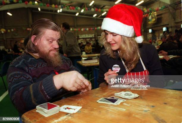 Rodney Baker a visitor to the Crisis Shelter in Bermondsey Street south London today plays a game of cards with volunteer Clare Cope The volunteer...