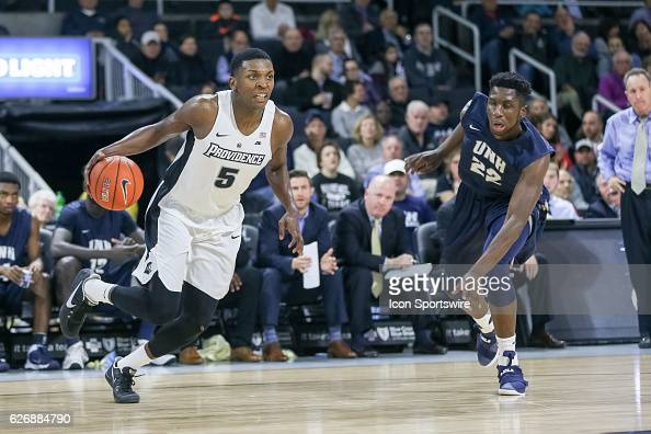 Rodney Bullock Forward for Providence College drives past David Watkins of University of New Hamphsire to the basket during the game between the...