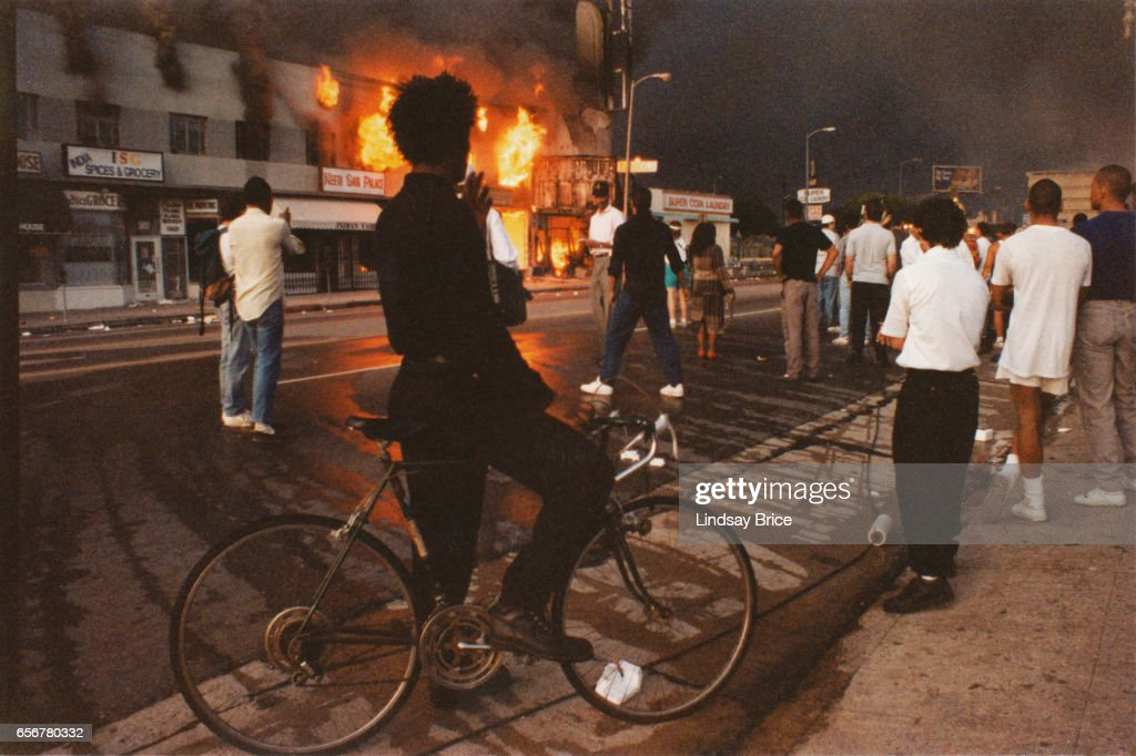 Rodney King Riot. A view of businesses beginning to burn on Pico Boulevard near Hayworth Avenue, onlookers gathering, a young man dressed in black pausing on bicycle watching fire during the Rodney King Riots, and the sky black with smoke in daylight on April 30, 1992 in Los Angeles, California.
