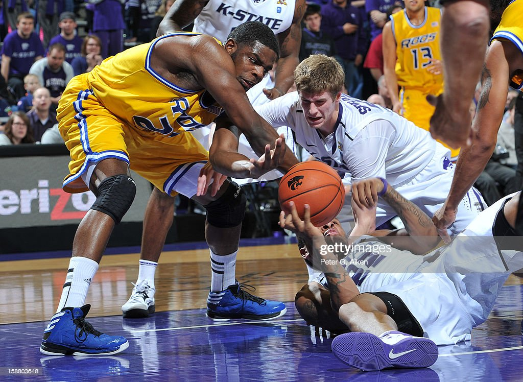 Rodney McGruder #22 and Will Spradling #55 of the Kansas State Wildcats scramble for a loose ball with forward Fred Chatmon #21 of the Missouri-Kansas City Kangaroos during the second half on December 29, 2012 at Bramlage Coliseum in Manhattan, Kansas. Kansas State defeated Missouri-Kansas City 52-44.