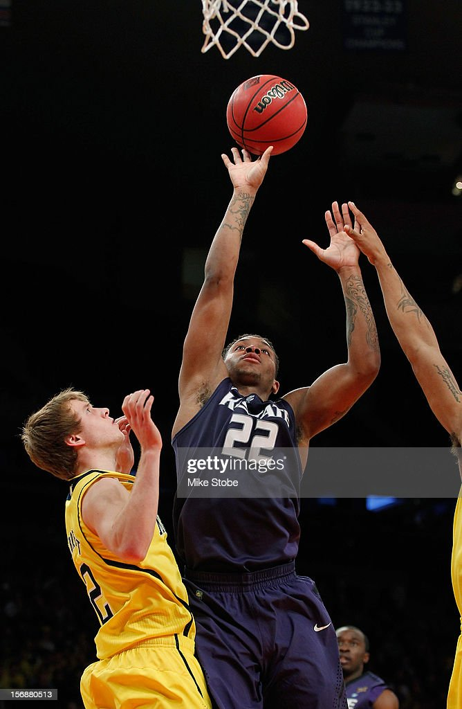 Rodney McGruder #22 of the Kansas State Wildcats drives towards the net against Caris LeVert #23 of the Michigan Wolverines at Madison Square Garden on November 23, 2012 in New York City. Michigan Wolverines defeated Kansas State Wildcats 71-57.