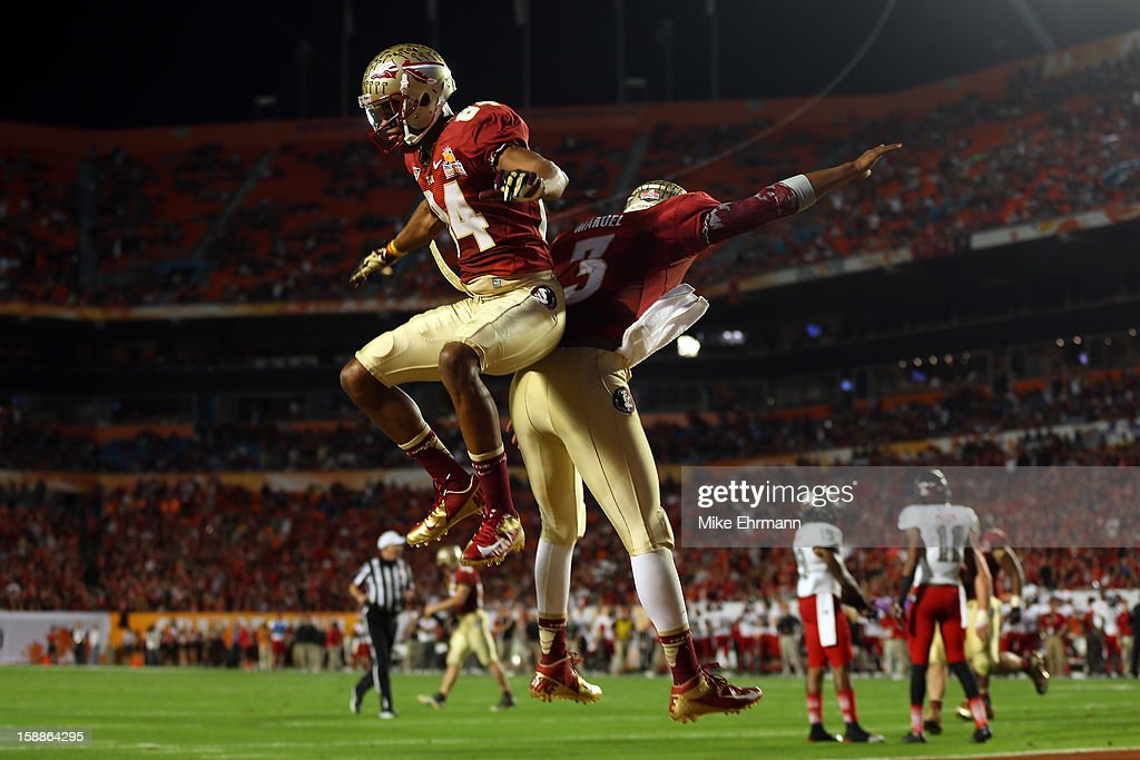Rodney Smith #84 and EJ Manuel #3 of the Florida State Seminoles celebrate after Manuel scored a 9-yard rushing touchdown in the fourth quarter against the Northern Illinois Huskies during the Discover Orange Bowl at Sun Life Stadium on January 1, 2013 in Miami Gardens, Florida.