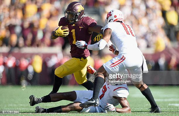 Rodney Smith of the Minnesota Golden Gophers carries the ball against Saquan Hampton and Isaiah Wharton of the Rutgers Scarlet Knights during the...