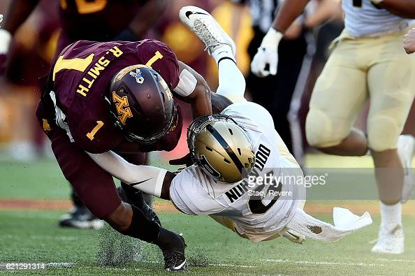 Rodney Smith of the Minnesota Golden Gophers is brought down by Myles Norwood of the Purdue Boilermakers during the first half of a game at TCF Bank...