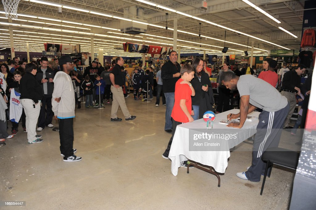 Rodney Stuckey, of the Detroit Pistons, autographs a ball and photo on April 13, 2013 at Dunhams sporting goods in Warren, Michigan.