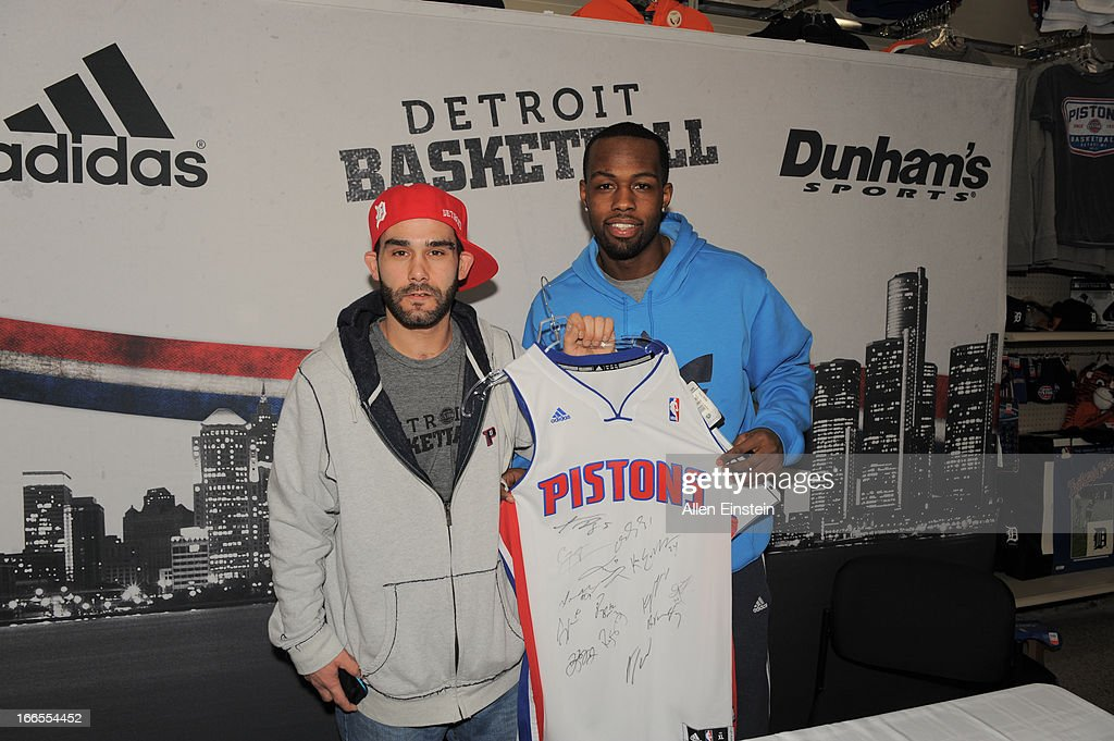 Rodney Stuckey, of the Detroit Pistons, poses with contest winner after a game of 'PIG' on April 13, 2013 at Dunhams sporting goods in Warren, Michigan.