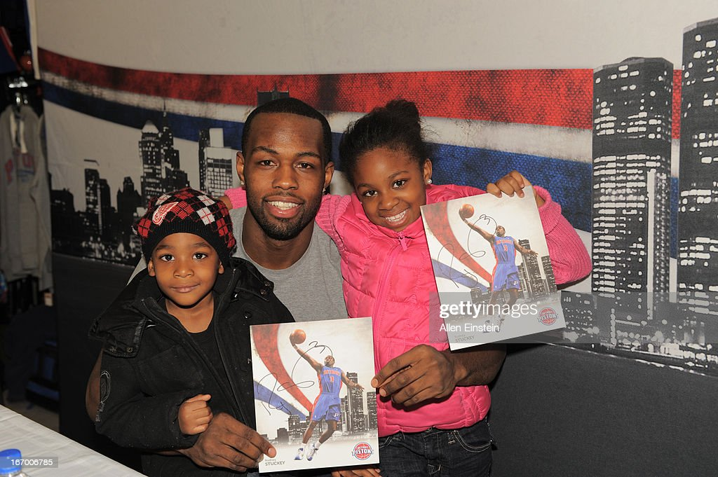 Rodney Stuckey #3 of the Detroit Pistons poses with fans while they show off their autographed photo on April 13, 2013 at Dunhams sporting goods in Warren, Michigan.