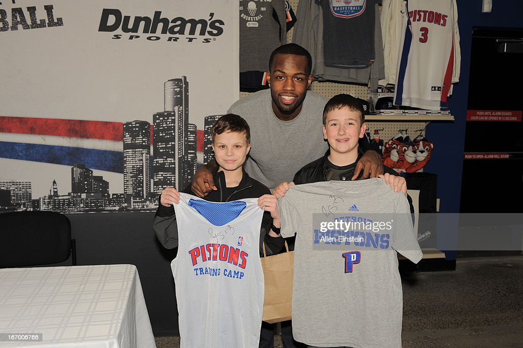 Rodney Stuckey #3 of the Detroit Pistons poses with fans who show off their autographed T-shirts on April 13, 2013 at Dunhams sporting goods in Warren, Michigan.