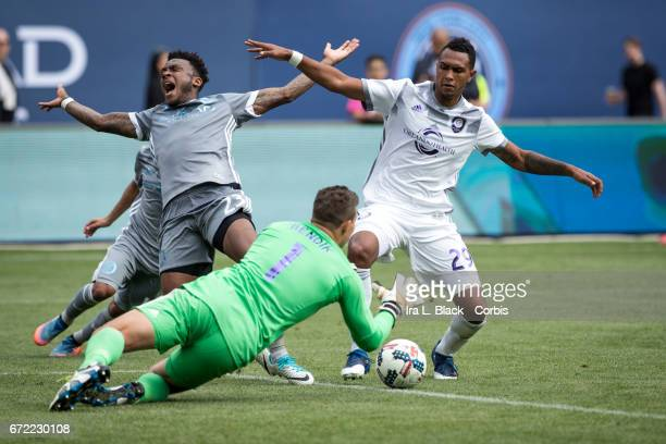Rodney Wallace of New York City FC reacts to a hit as he drives for the goal with Goalkeeper Joe Bendik and Tommy Redding during the MLS match...