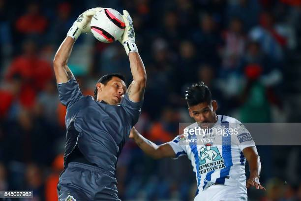 Rodolfo Cota of Chivas catches the ball in the arir againts Franco Jara of Pachuca during the 8th round match between Pachuca and Chivas as part of...