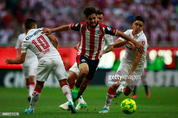 Rodolfo Pizarro of Chivas fights for the ball with Efrain Velarde and Antonio Naelson of Toluca during the semi final second leg match between Chivas...