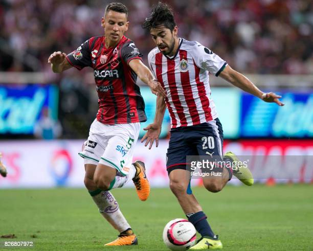 Rodolfo Pizarro of Chivas fights for the ball with Igor Lichnovsky of Necaxa during the third round match between Chivas and Necaxa as part of the...