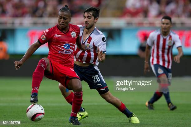 Rodolfo Pizarro of Chivas fights for the ball with Pedro Aquino of Lobos during the 11th round match between Chivas and Lobos BUAP as part of the...