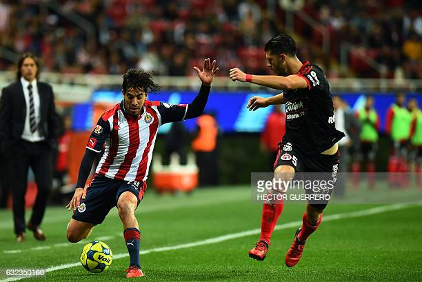 Rodolfo Pizarro of Guadalajara vies for the ball with Guido Rodriguez of Tijuana during their Mexican Clausura 2017 tournament football match at...