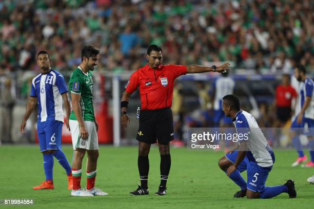 Rodolfo Pizarro of Mexico and Ever Alvarado of Honduras are warned by the Referee Walter Lopez during the CONCACAF Gold Cup 2017 quarterfinal match...
