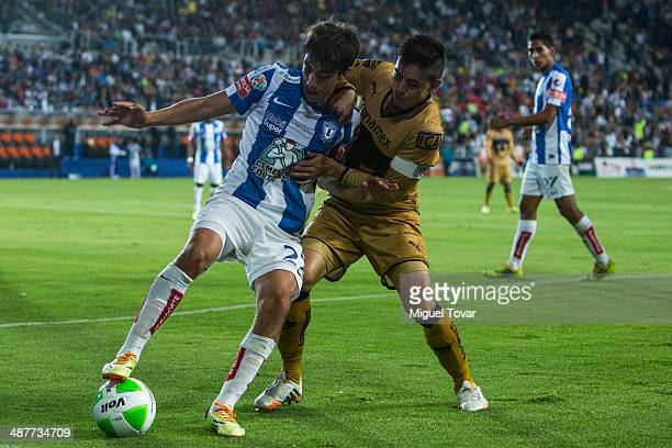 Rodolfo Pizarro of Pachuca fights for the ball with Efrain Velarde of Pumas during the Quarterfinal first leg match between Pumas UNAM and Pachuca as...