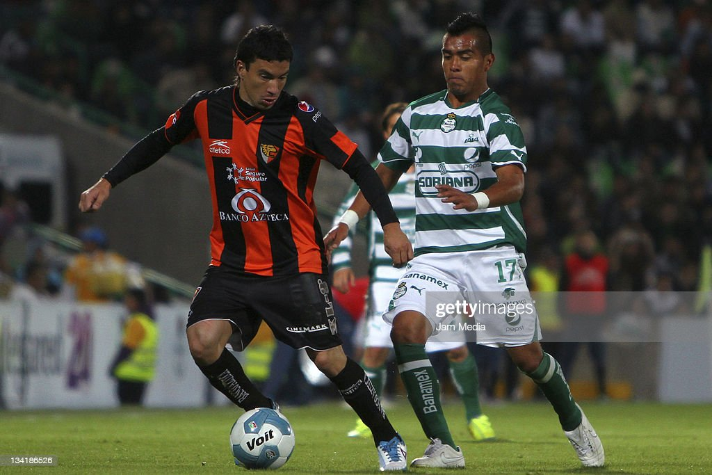 Rodolfo Salinas of Santos struggles for the ball with Jorge Rodriguez of Jaguares during a quarter final match as part of the Apertura 2011 at Corona...