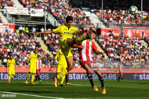 Rodri Hernandez of Villarreal CF competes for the ball with Pere Pons of Girona FC during the La Liga match between Girona and Villarreal at Estadi...