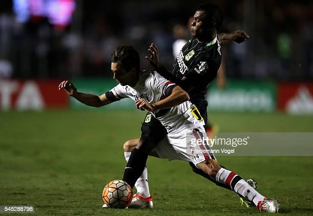 Rodrigo Caio of Sao Paulo fights for the ball with Diego Polenta of Atletico Nacional during semifinal first leg match of Copa Bridgestone...