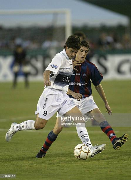 Rodrigo Copiz of Club Olimpia controls the ball in front of Gonzalo Rodriguez of San Lorenzo de Almagro during the Recopa Final at the Los Angeles...