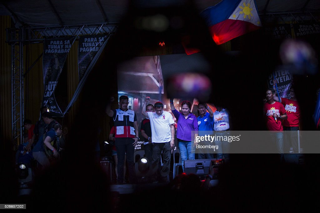 Rodrigo Duterte, mayor of Davao City and presidential candidate, center, gestures with the crowd during a campaign rally in Manila, the Philippines, on Sunday, May 1, 2016. Duterte, the crime-fighting mayor who is favored to win the Philippines May 9 presidential election, failed to declare tens of millions of dollars in assets, according to records released by a senator supporting rival candidate Grace Poe. Photographer: Taylor Weidman/Bloomberg via Getty Images