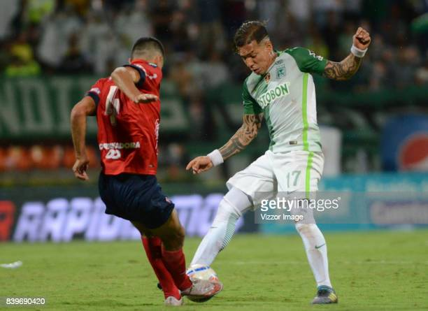 Rodrigo Erramuspe of Independiente Medellin vies for the ball with Dayro Moreno of Atletico Nacional during a match between Independiente Medellin...