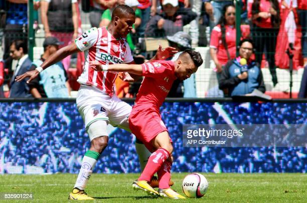 Rodrigo Gomez of Toluca is marked by Bryan Beckeles of Necaxa during their Mexican Apertura football tournament match at the Nemesio Diez stadium in...