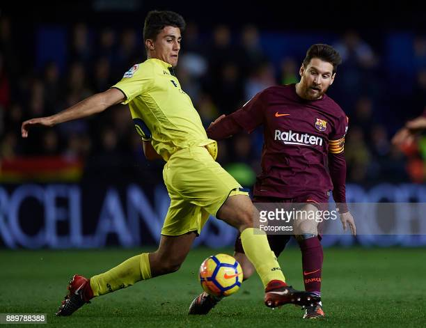 Rodrigo Hernandez of Villarreal competes for the ball with Lionel Messi of Barcelona during the La Liga match between Villarreal and Barcelona at...